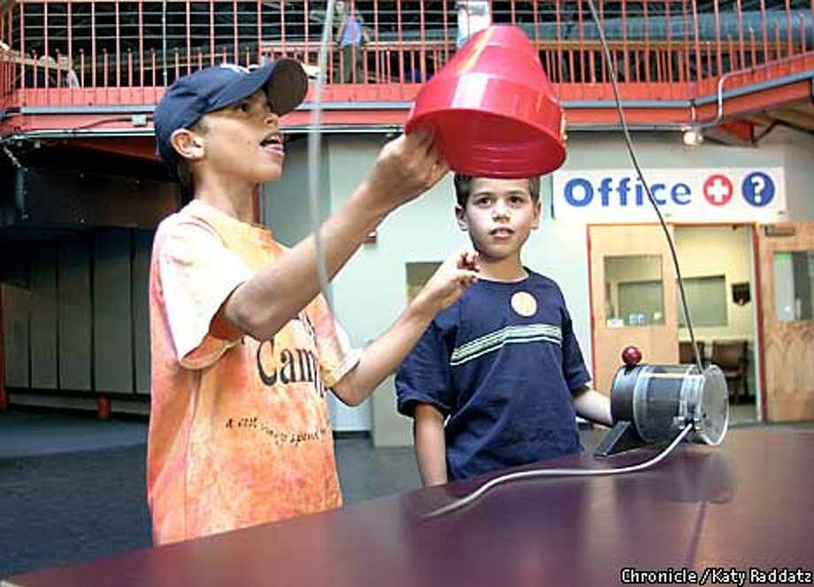 """PHOTO BY KATY RADDATZ--THE CHRONICLE  The Exploratorium in San Francisco. SHOWN: L to R--Jacob Guggenheim, Aaron Guggenheim, twin brothers from Palo Alto, age 10. They're checking out the """"String Shooter"""", which shows wave motion and curvatures."""