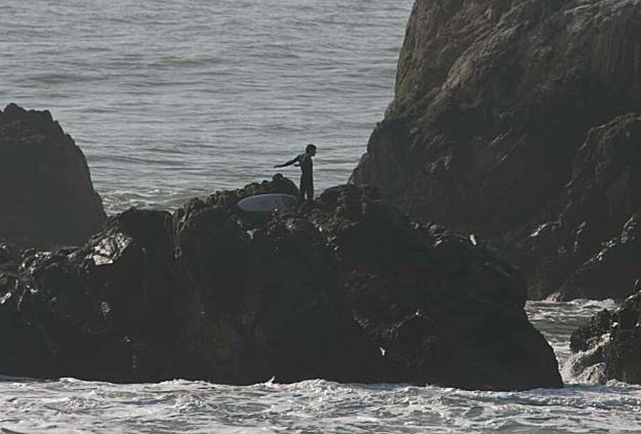 A surfer waits for a Coast Guard helicopter rescue after he became stranded on a rock near Lands End in San Francisco, Calif., on Monday, Jan. 4, 2010. The unidentified surfer was transferred safely back to the shore around 12:15 p.m. Photo: Gary Jung, Special To The Chronicle