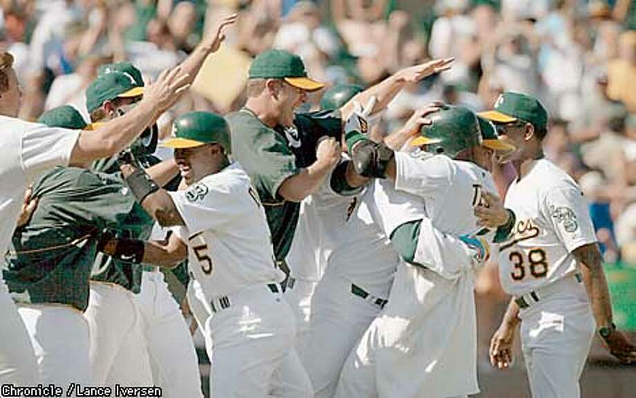 A's Miguel Tajada (second from right) is mobbed by his teammates after hitting the game winning single that ties the 1906 White Soxs and the 1947 Yankee consecutive winning streaks at 19 games. The Athletics defeated the Kansas city Royals 7-6.  By LANCE IVERSEN/SAN FRANCISCO CHRONICLE Photo: LANCE IVERSEN