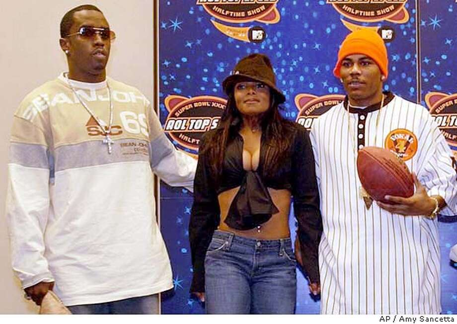 Entertainers Sean P. Diddy Combs, left, and Nelly, right, settle Janet Jackson in between them as they stand for a small group of photographers following a news conference touting the halftime show of Super Bowl XXXVIII in Houston on Thursday, Jan. 29, 2004. Jackson did not attend the news conference. (AP Photo/Amy Sancetta) Photo: AMY SANCETTA