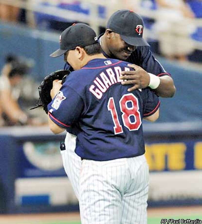 Minnesota Twins closer Eddie Guardado (18) gets a hug from teammate David Ortiz after they beat the Milwaukee Brewers, 4-3, Sunday, June 30, 2002, in Minneapolis. (AP Photo/Paul Battaglia) Photo: PAUL BATTAGLIA