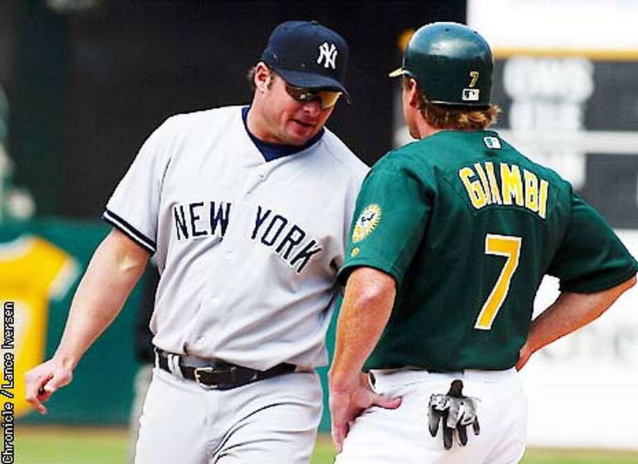 Jason Giambi greets his younger brother Jeremy Giambi at first base late into thursday's game. The Athletics won 6-2 in the finial game of a three game stand. BY LANCE IVERSEN/SAN FRANCISCO CHRONICLE Photo: LANCE IVERSEN
