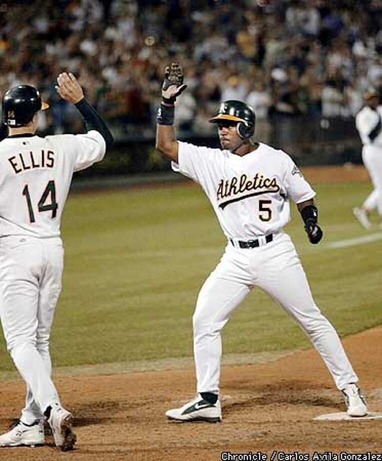 ATHLETICS19-C-18SEP02-SP-CG --- Ray Durham high fives Mark Ellis after Durham hit a three-run homerun in the bottom of the fourth inning to break a 4-4 tie making the score 7-4 athletics against the Anaheim Angels at Network Associates Coliseum on Wednesday, September 18, 2002. (CARLOS AVILA GONZALEZ/SAN FRANCISCO CHRONICLE)