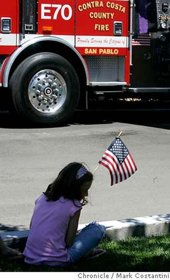 Paige Holland, 8, who's mother went to high school with Matthew, sits outside memorial with a flag near Matthew's fire engine. The procession for Captain Mathew Burton will start at 1 p.m., beginning from Muir Road at Glacier Drive in Martinez and ending at Moore Funeral Home located at 1390 Monument Boulevard in Concord.  PHOTO: Mark Costantini / The Chronicle Photo: MARK COSTANTINI