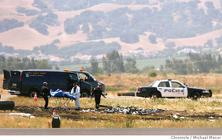 Investigators on the scene, the Alameda County Coroner removes the bodies of the two aboard the aircraft. A plane carrying two crashed this morning around 8:30am killing the two occupants onboard.The small plane taking off from the Livermore Municipal Airport. Photographed in, Livermore, Ca, on 6/16/07. Photo by: Michael Macor/ The Chronicle Photo: Michael Macor