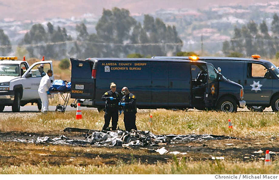 Investigators on the scene, the Alameda County Coroner removes the bodies of the two aboard the aircraft. A plane carrying two, crashed this morning around 8:30am killing the two occupants onboard. The small plane taking off from the Livermore Municipal Airport. Photographed in, Livermore, Ca, on 6/16/07. Photo by: Michael Macor/ The Chronicle Photo: Michael Macor