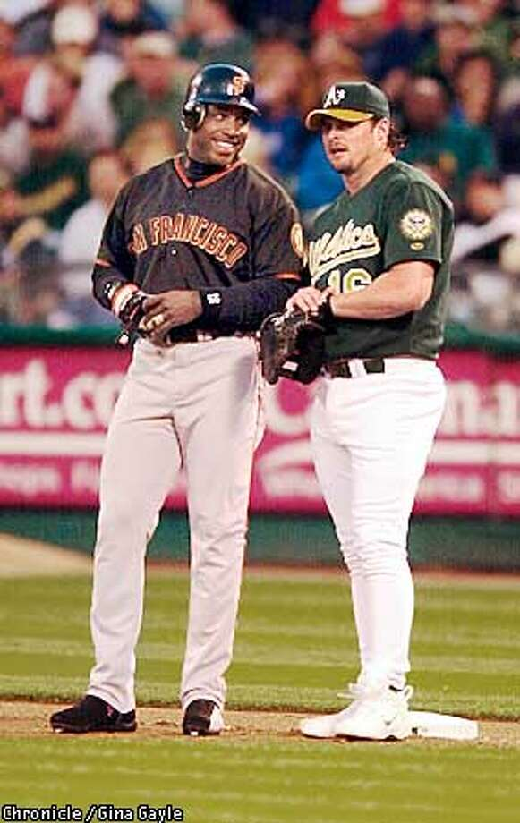 Oakland Athletics slugger, Jason Giambi, right, and San Francisco Giants, Barry Bonds, left, share a little talk at first base during the fifth inning at Network Associates Coliseum during the A's game against the San Francisco Giants on Friday night, June 08, 2001. (Photo by Gina Gayle/The San Francisco Chronicle) Photo: GINA GAYLE