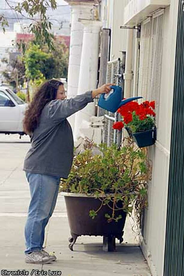 Coral Romero, owner of Latch Tile in Bayview of SF waters her flowers above a bath tub turned into a planter in front of her business. She was warned of a impending $500. fine if she doesn't get a permit or remove the plants. BY ERIC LUSE/THE CHRONICLE Photo: ERIC LUSE