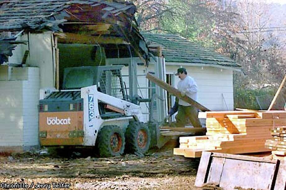 A worker demolished a house on a Danville property as others prepared foundations for the much larger home that will replace it. Chronicle photo by Jerry Telfer