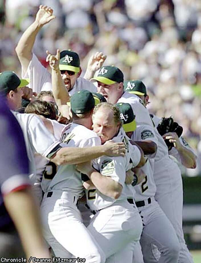 The Oakland A's celebrated on the pitcher's mound after shutting out the Rangers to win the division. Chronicle photo by Deanne Fitzmaurice
