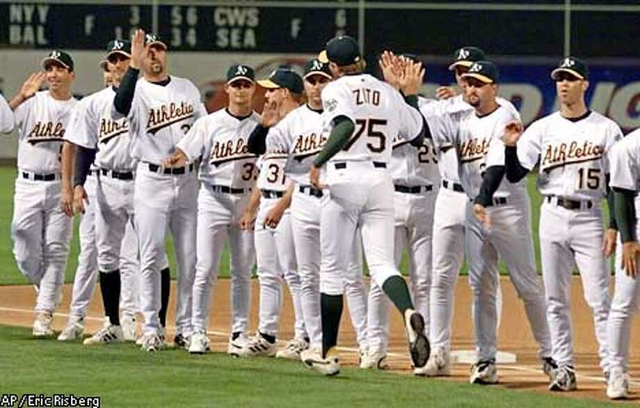 Oakland Athletics pitcher Barry Zito is greeted by his teammates during the opening day lineup introduction before the A's opener against the Texas Rangers in Oakland, Calif., Monday April 1, 2002.(AP Photo/Eric Risberg) Photo: ERIC RISBERG