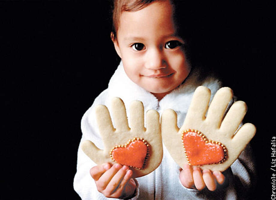Maya Anonizado holds up hand-shaped sugar cookies with cookie hearts in the center. Chronicle photo by Liz Hafalia