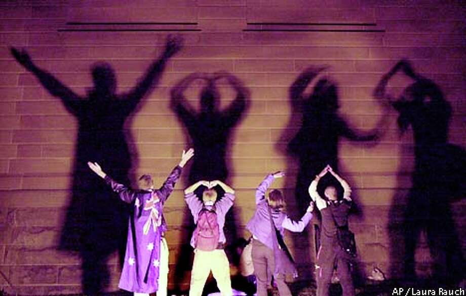 "Short of people to spell ""Olympics,"" these youths settled for ""YMCA"" in front of spotlights at the Sydney Museum of Contemporary Art. Associated Press photo by Laura Rauch"