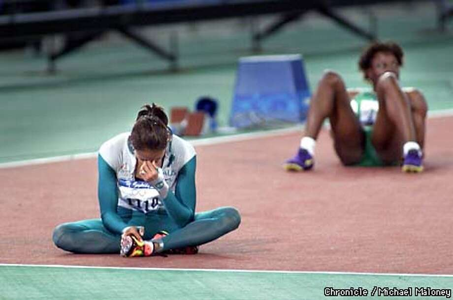 Gold medalist Cathy Freeman of Australia sat down after the 400-meter final, as did (background) seventh-place finisher Falilat Ogunkoya of Nigeria. Chronicle photo by Michael Maloney