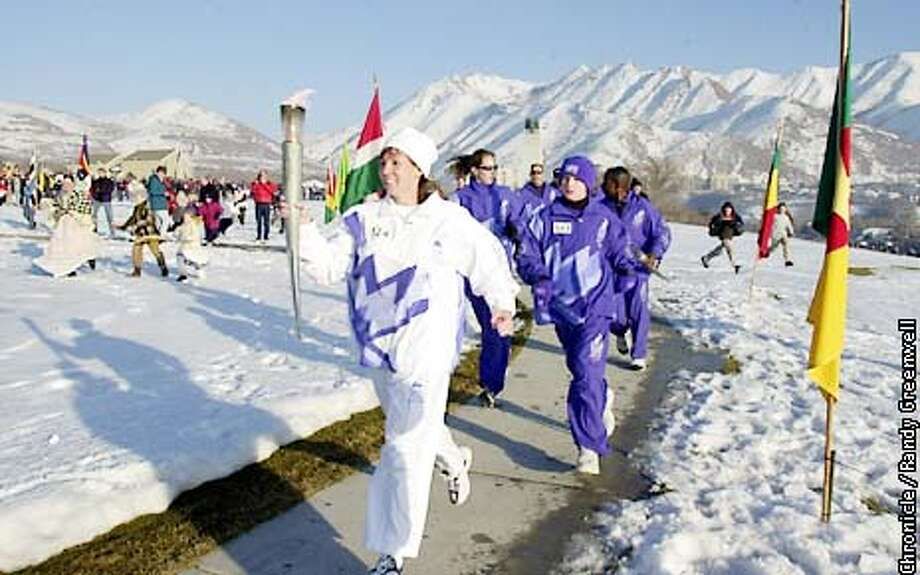 "Courtney Johnson of Salt Lake City winds through This Is The Place Heritage Park, ushering the Olympic torch into Salt Lake City Thursday, February 7, 2002. The park is supposed to be where Brigham Young stopped after crossing the Wasatch Mountains and exclaimed, ""This is the place"" where he would settle. The 2002 Winter Olympics takes place in Salt Lake City, Utah. Randy Greenwell/The Chronicle Photo: Randy Greenwell"