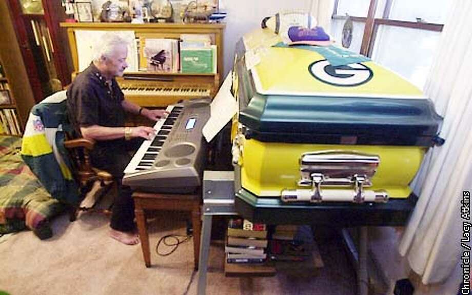 """Rocky Rockstroh, 68, a die hard Green Bay Packer fan plays the electric piano in his living room next to his yellow and green castget, at his home in Green Bay. """"Who says you cann't take in with you"""", says Rockstroh who has been a packer fan for 61 years.  CHRONICLE PHOTOGRAPHER/ LACY ATKIN Photo: Lacy Atkins"""