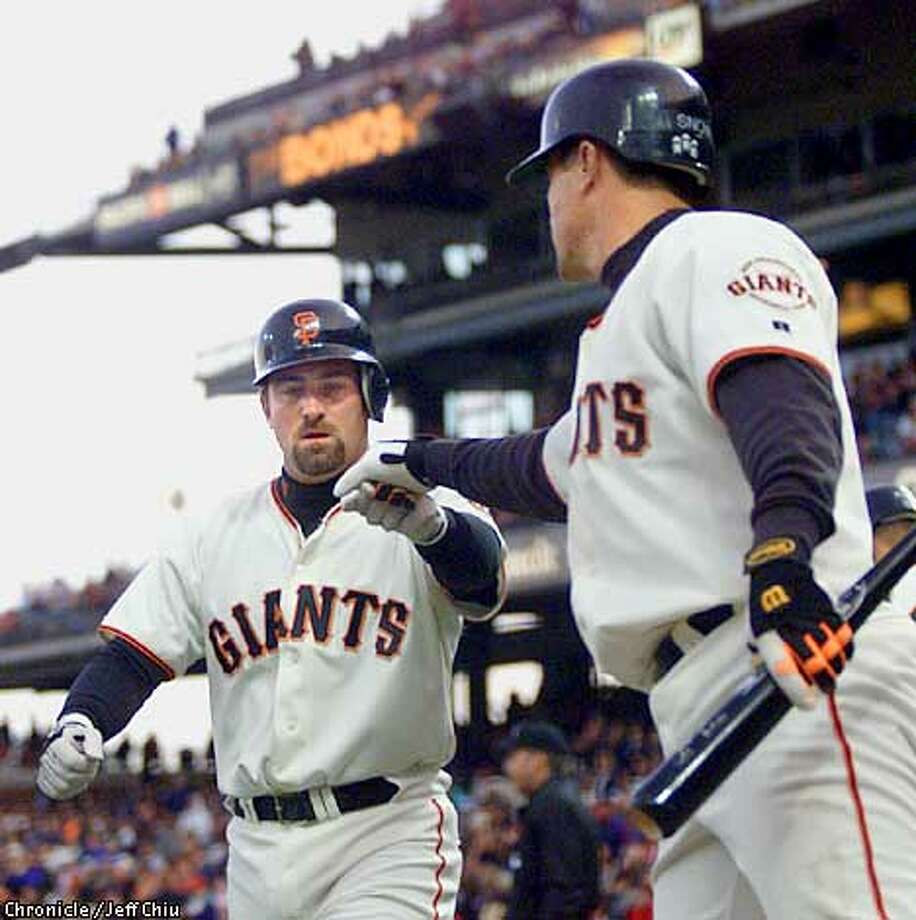 Rich Aurilia, left, greeted by J.T. Snow, scored in the first inning last night to give the Giants an early lead. Chronicle photo by Jeff Chiu