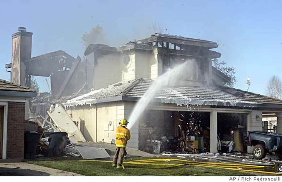 A firefighter pours water on a home that had been engulfed in flames after it was struck by a single engine plane in Roseville, Calif., Sunday, Feb. 12, 2006. The pilot of the plane was killed in the crash.(AP Photo/Rich Pedroncelli) Photo: RICH PEDRONCELLI