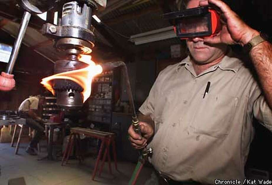 Park Supervisor, Roger Epperson, says being a park ranger requires that you be a jack of all trades. While Epperson (right) works on repairing the chuck on the park's drill press, park ranger Monique Looney cleans chain saw chains in the tool shed at the Black Diamond Mines Regional Preserve. SAN FRANCISCO CHRONICLE PHOTO BY KAT WADE Photo: KAT WADE