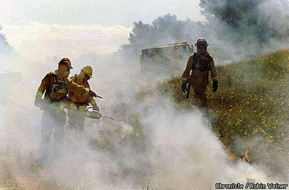 """Lt. Robert Bouska (right) of the Regional Parks Fire and Rescue surveyed the controlled burn of yellow star thistle in Briones Regional Park as firefighters Ben Castillo (left) and Randy Trumpf set the blaze using a ``drip torch."""" Chronicle Photo by Robin Weiner"""