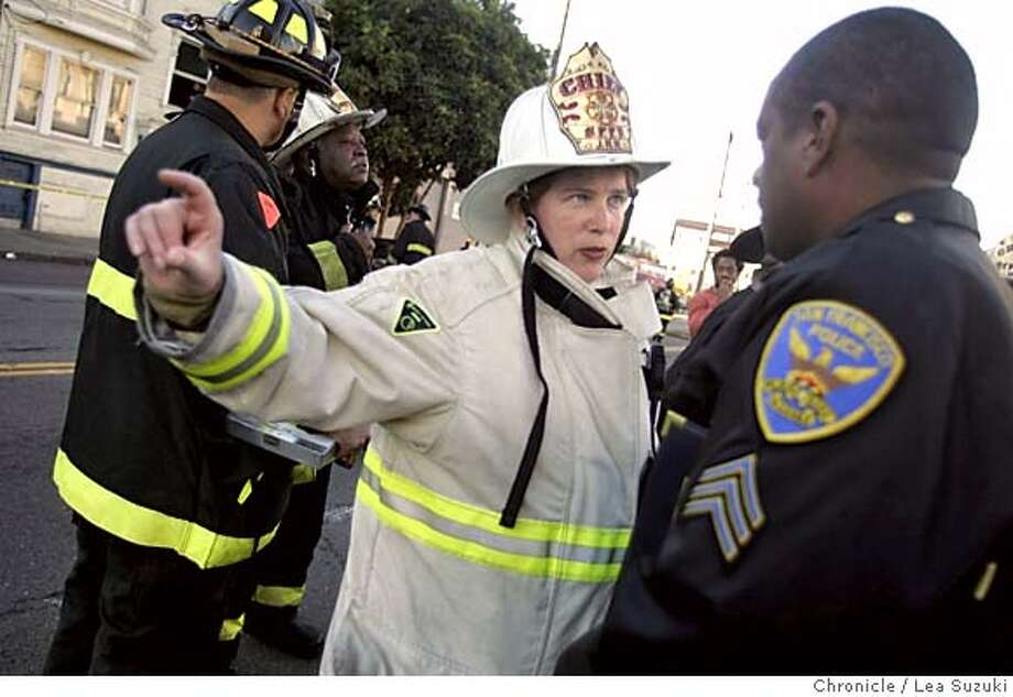 Fire Chief Joanne Hayes-White talks to an officer on South Van Ness. Firefighters work to put out a blaze on Shotwell between 15th and 16th Streets in San Francisco Monday afternoon. Photo taken on 10/31/05 in San Francisco, CA. Photo by Lea Suzuki/ The San Francisco Chronicle Photo: Lea Suzuki