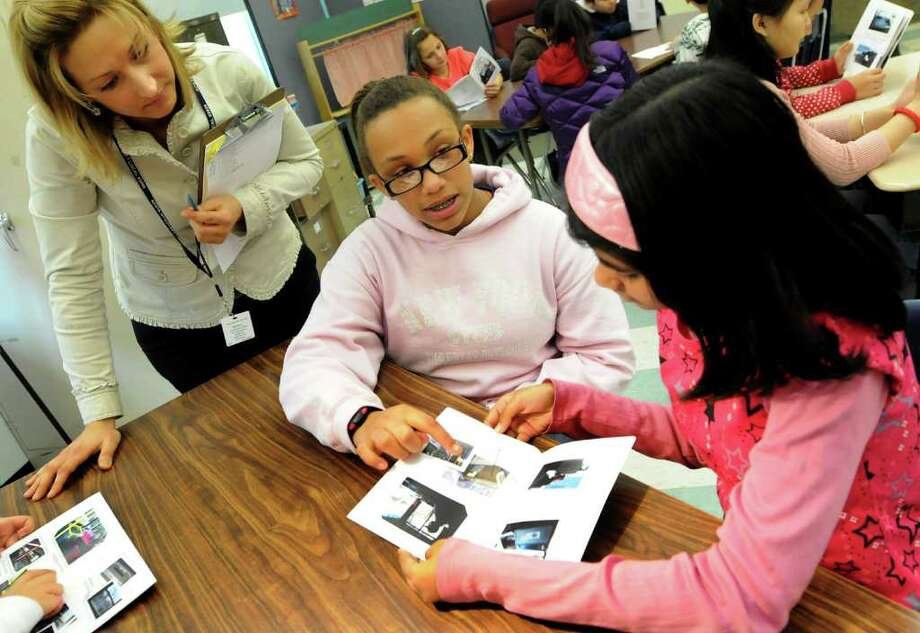 Sarha Smith-Moyo, 11, of The Albany School of the Humanities, center, shows Sadia Alam, 12, a booklet on riding the CDTA bus on Tuesday, Feb. 14, 2012, at Giffen Memorial Elementary School in Albany, N.Y. Looking on is ESL teacher Betsey Domenico, left. (Cindy Schultz / Times Union) Photo: Cindy Schultz / 00016426A