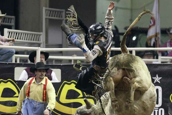 Ty Pozzobon gets tossed from Dirty White Bull during the bull riding competition at the 2012 San Antonio Stock Show & Rodeo on Tuesday, Feb. 14, 2012.