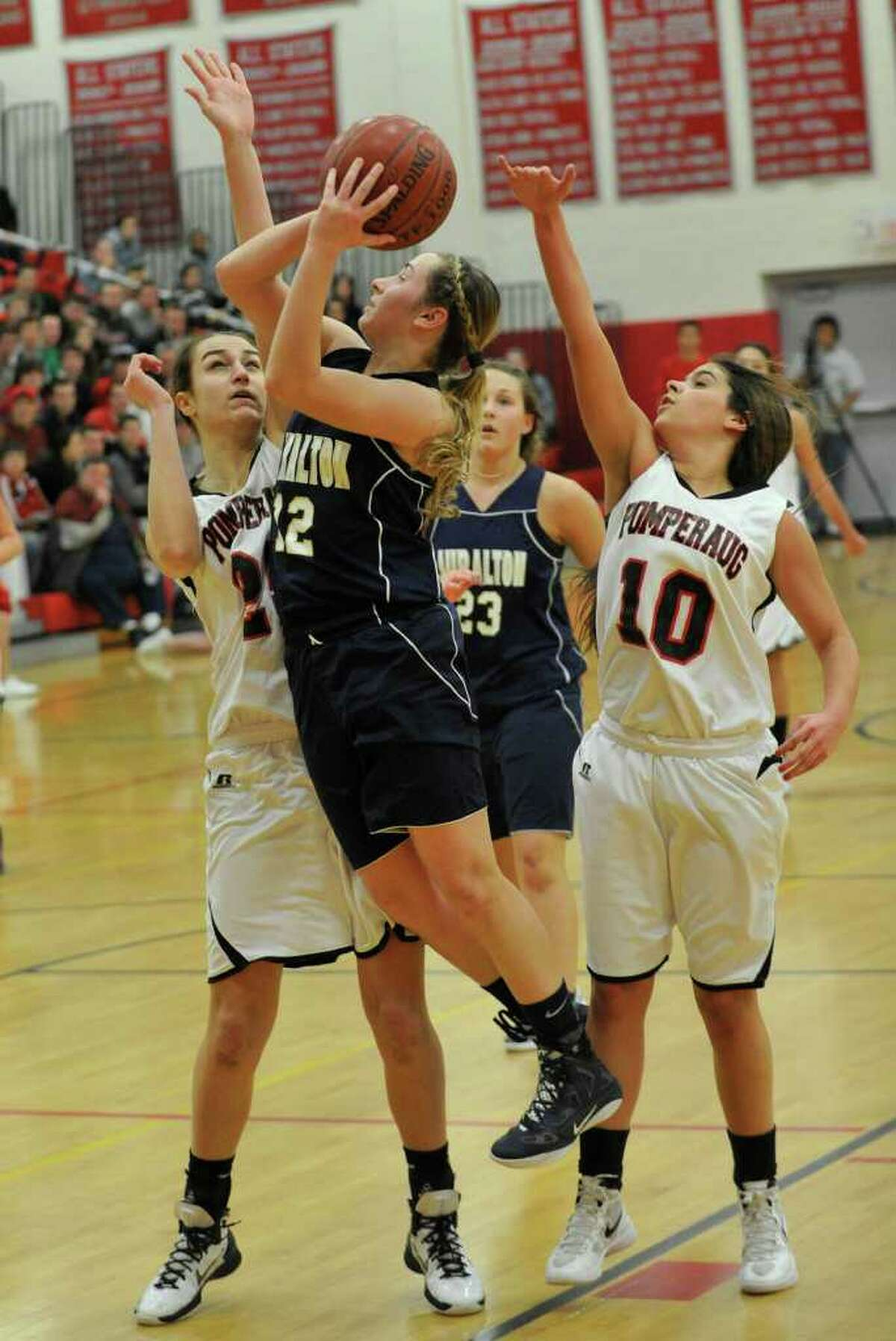 Lauralton Hall's Marisa Dowling shoots while under pressure from Pomperaug's Lauren Baranowski, left, and Hannah Metcalf during their game at Pomperaug High School in Southbury on Tuesday, Feb. 14, 2012. Lauralton Hall won 52-47.