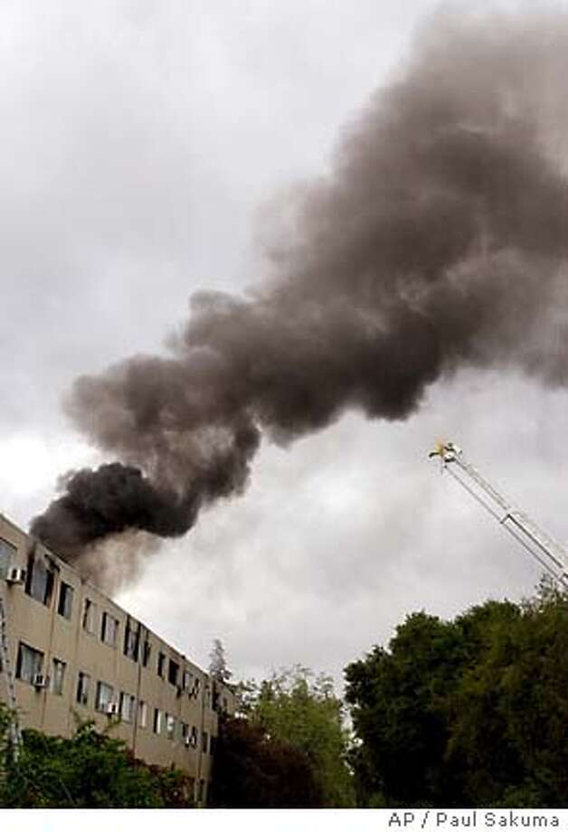 Smoke billows from the top floor of an burning apartment complex in San Jose, Calif., Wednesday, March 23, 2005. A spokesman for the San Jose Fire Department said about 100 people in the complex have been forced out of their homes by the fire. (AP Photo/Paul Sakuma) Photo: PAUL SAKUMA