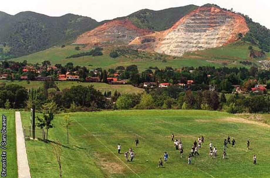 Diablo View Middle School pupils frolic in a game of soccer in the shadow of Mount Zion where RMC Lonestar Quarry sits on the base of the the east face of the mountain adjacent to Black Point and Mount Diablo. Save Mount Diablo and RMC Lonestar Qaurry are in a squabble over who will get control of 40 acres near Mount Zion's peak. (The green land pictured between the two rock faces) The community of Clayton is nestled in between the school children and Mount Zion. (Chronicle Photo by Sam Deaner) Photo: SM DEANER