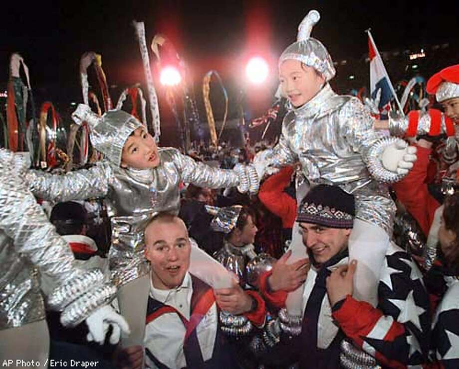 US athletes carry little Japanese performers on their shoulders as they celebrate the closing of the XVIII Winter Olympic Games at the Minami Nagano Sports Park in Nagano Sunday, Feb. 22, 1998. (AP Photo/Eric Draper) Photo: ERIC DRAPER