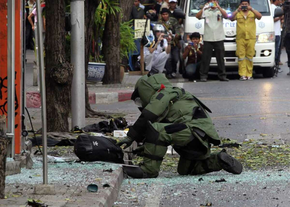 A Thai Explosive Ordnance Disposal (EOD) official examines a backpack that was left on the bomb site by a suspect bomber in Bangkok, Thailand Tuesday, Feb. 14, 2012. Thai police say two explosions have occurred in a Bangkok neighborhood. But it was not immediately clear what caused the blasts or wether there were an fatalities. (AP Photo/Apichart Weerawong)