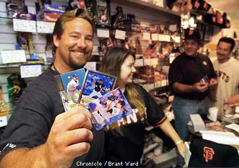 GIANTS TRADE 2/31AUG97/MN/WARD--Jim Towan, left, owner of the Ballpark Sports Cards store in San Francisco is smiling after finding cards for the new Giants acquisitions...Danny Darwin, Roberto Hernandez and Wilson Alvarez. He and his wife Renee and other serious Giant fans were celebrating Thursday and looking for those elusive cards. By Brant Ward/Chronicle
