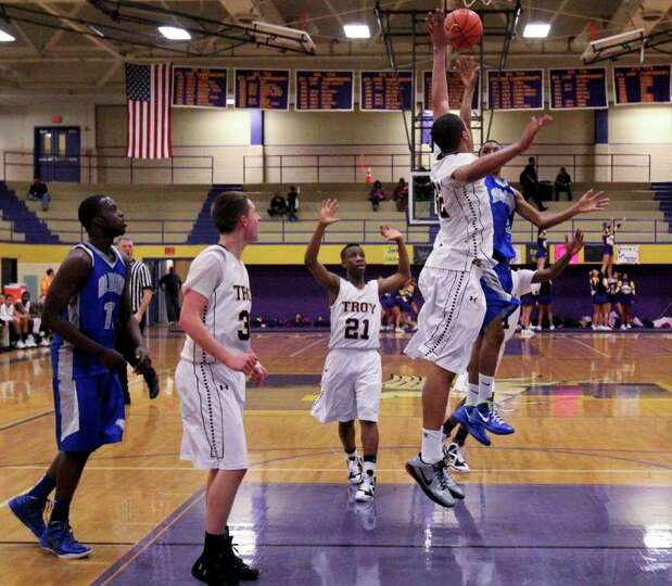 Javion Ogunyemi, of Troy High School, center, tries to block the shot of Dan Brown, of Albany High S