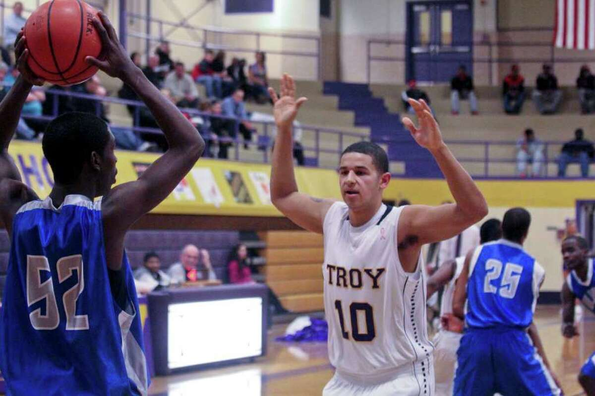 Preston Vanterpool, of Albany High School, left, looks for an open teammate as Khalil Paul, of Troy High School, center, tries to block him at the Albany High School vs. Troy High School basketball game at Troy High on Tuesday, Feb. 14, 2012. (Erin Colligan / Special To The Times Union)