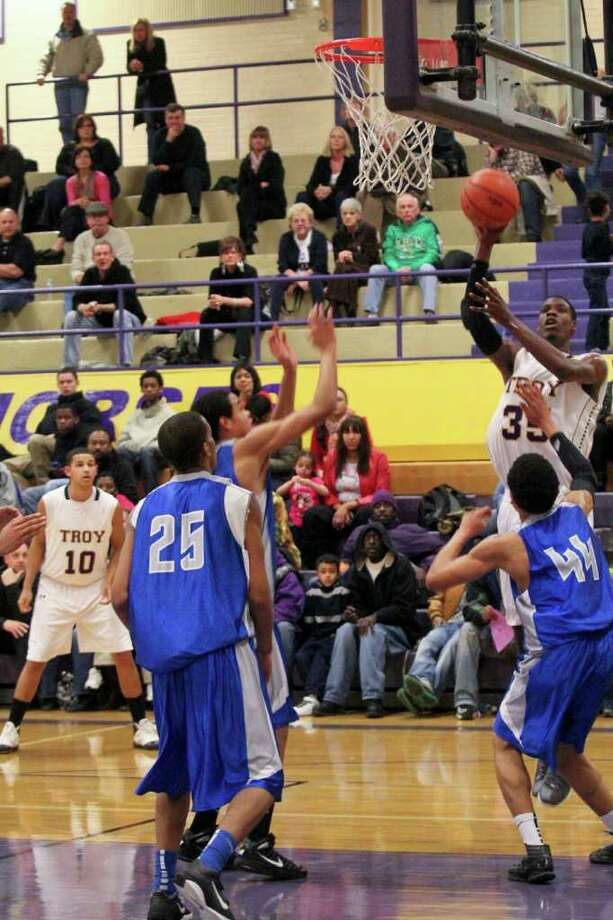 Kareem Brown, of Troy High School, right rear, shoots the ball as Arthur Ware, of Albany High, right, reaches guards the basket at the Albany High School vs. Troy High School basketball game at Troy High on Tuesday, Feb. 14, 2012. (Erin Colligan / Special To The Times Union)