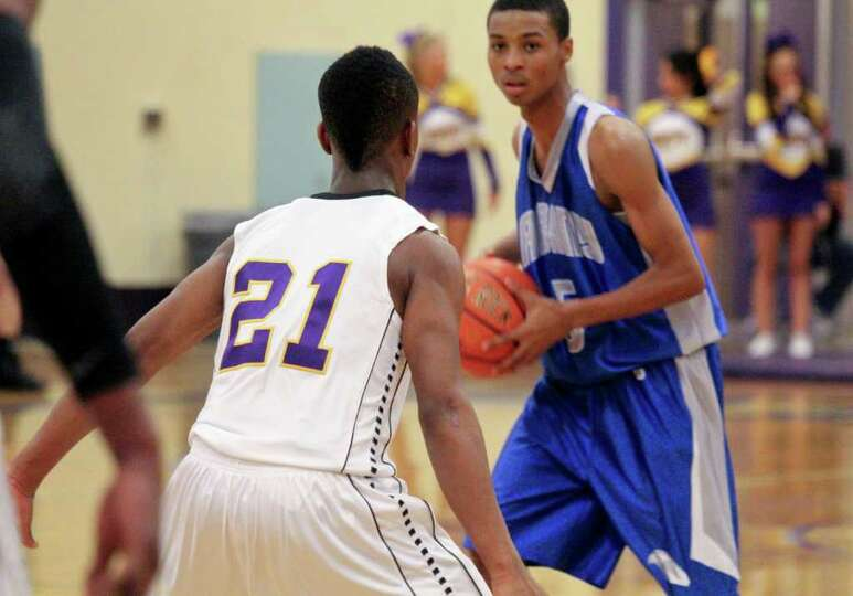 Isiah Dobere, of Troy High School, center, guards against Dan Brown, of Albany High School, right re
