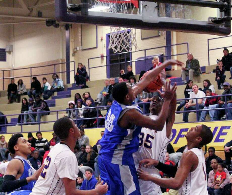 Kareem Brown, of Troy High School, center right, shoots the ball as (PLAYER 00 NOT ON ROSTER), of Albany High, right, tries to block his shot at the Albany High School vs. Troy High School basketball game at Troy High on Tuesday, Feb. 14, 2012. (Erin Colligan / Special To The Times Union)