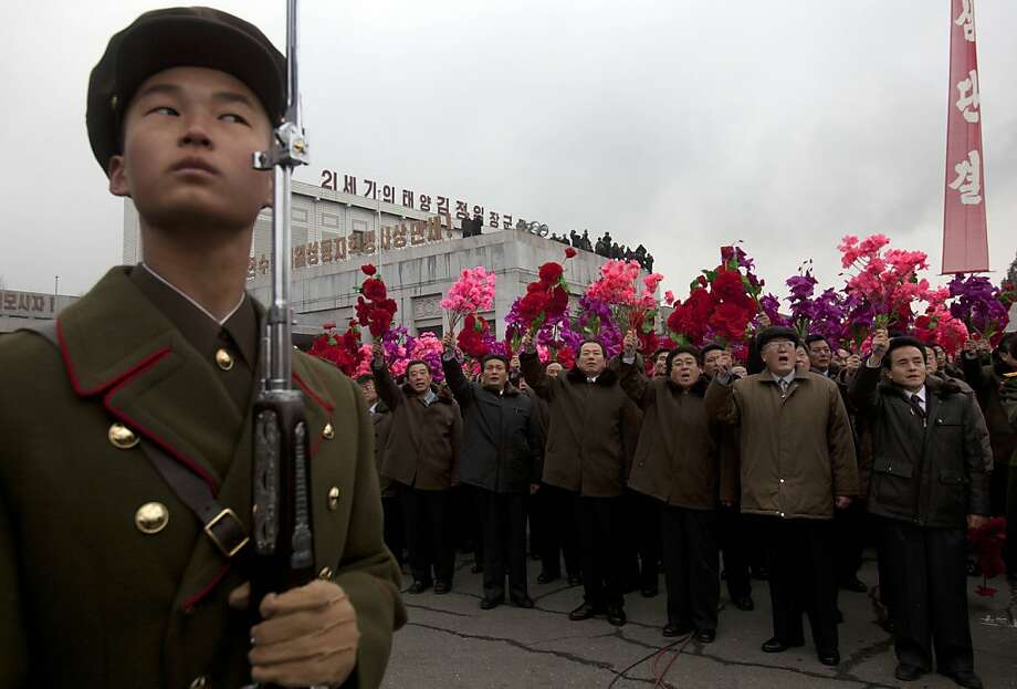A North Korean stands at attention as others cheer during the unveiling of a new bronze statue depicting the late leader Kim Jong Il and his father Kim Il Sung at Mansudae Art Studio in Pyongyang Tuesday, Feb. 14, 2012. As North Koreans prepare for what would have been the 70th birthday of late leader Kim Jong Il this week, the country's state media have gone to great lengths to build up the man who led the nation for 17 years until his death in December. (AP Photo/David Guttenfelder) Photo: David Guttenfelder, Associated Press
