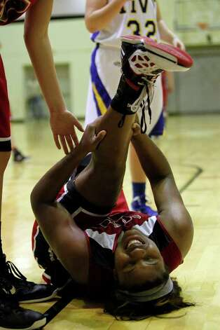 New Braunfels Canyon's Chamaya Turner goes down after a leg injury against Kerrville Tivy during a girls' basketball Class 4A playoff game at Littleton Gymnasium on Tuesday, Feb. 14, 2012. Turner quickly recovered and led New Braunfels Canyon to a win over Kerrville Tivy, 54-45. MICHAEL MILLER / mmiller@express-news.net Photo: Michael Miller, Express-News / © 2012 San Antonio Express-News