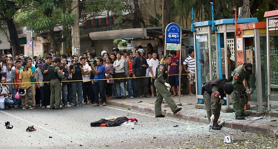 Thai bomb squad officials inspect the site of an explosion in Bangkok on February 14, 2012.  Three minor blasts rattled the Thai capital Bangkok, leaving a foreigner seriously wounded when a grenade he was suspected of carrying exploded, police said. Photo: Nicolas Asfouri, AFP/Getty Images