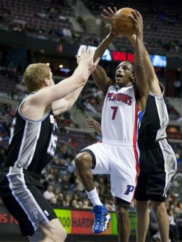 Detroit Pistons' Brandon Knight (7) takes a shot against San Antonio Spurs' Matt Bonner, left, and Tony Parker, right, in the second half of an NBA basketball game Tuesday, Feb. 14, 2012, in Auburn Hills, Mich. The Spurs defeated the Pistons 99-95. (AP Photo/Duane Burleson) (AP)
