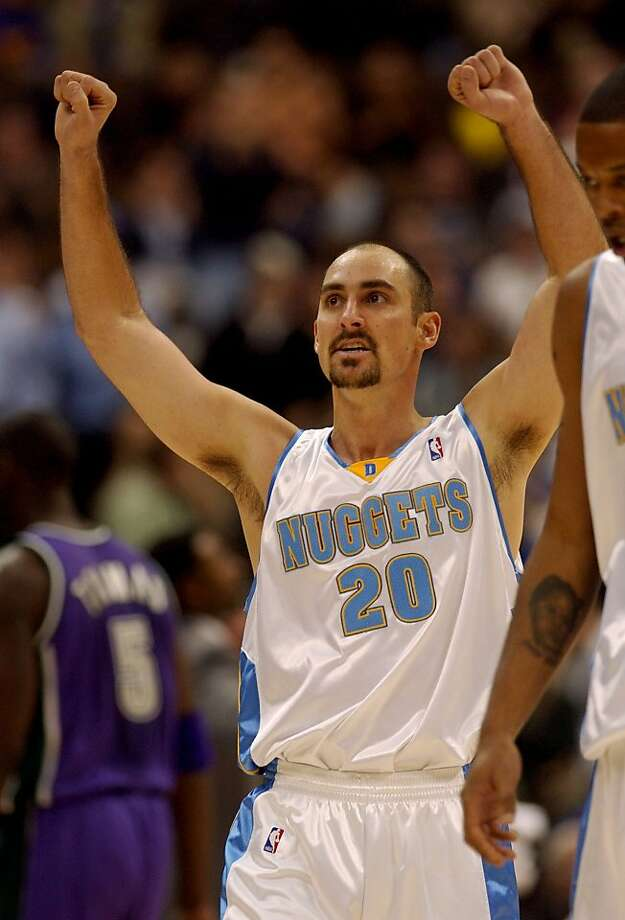 Denver Nuggets guard Jon Barry, front, raises his arms in victory after the Nuggets held off the Milwaukee Bucks 94-86 in Denver on Wednesday, Nov. 19, 2003. Bucks forward Tim Thomas, back, heads to the bench in the background. Photo: David Zalubowski, ASSOCIATED PRESS