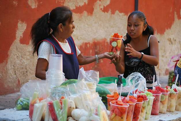 A young woman buys fresh fruit on the street. In San Miguel de Allende the climate is mild nearly year round. Photo: Maribeth Mellin, Special To SFGate