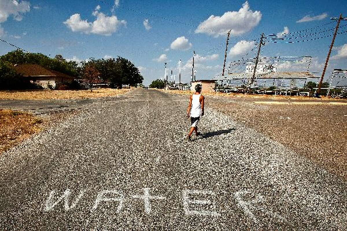 Jesus Landeros, 14, walks to the city pool in Robert Lee on Aug. 9, 2011, past a spray painted sign directing firefighters to a water source to fill their tankers while fighting the recent Wildcat Fire that threatened the town and burnt 160,000 acres. The city's pool was used by a firefighting helicopter when it scooped several hundred gallons to be dropped on a nearby wildfire that threatened the town and burnt 160,000 acres. (Michael Paulsen / Houston Chronicle)