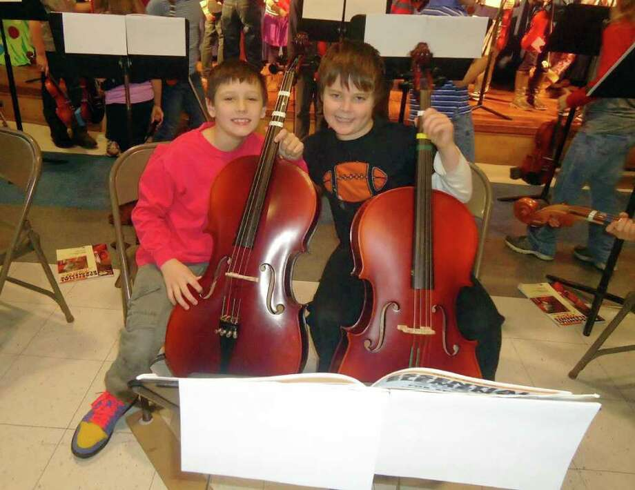 Carter Shea and Matthew Felske tune their cellos before the concert. Photo: Contributed Photo