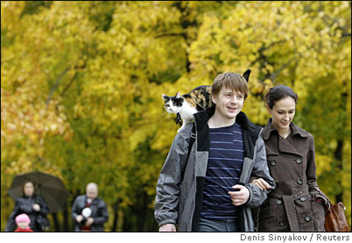 People walk, with a cat, in Kolomenskoye Park in Moscow