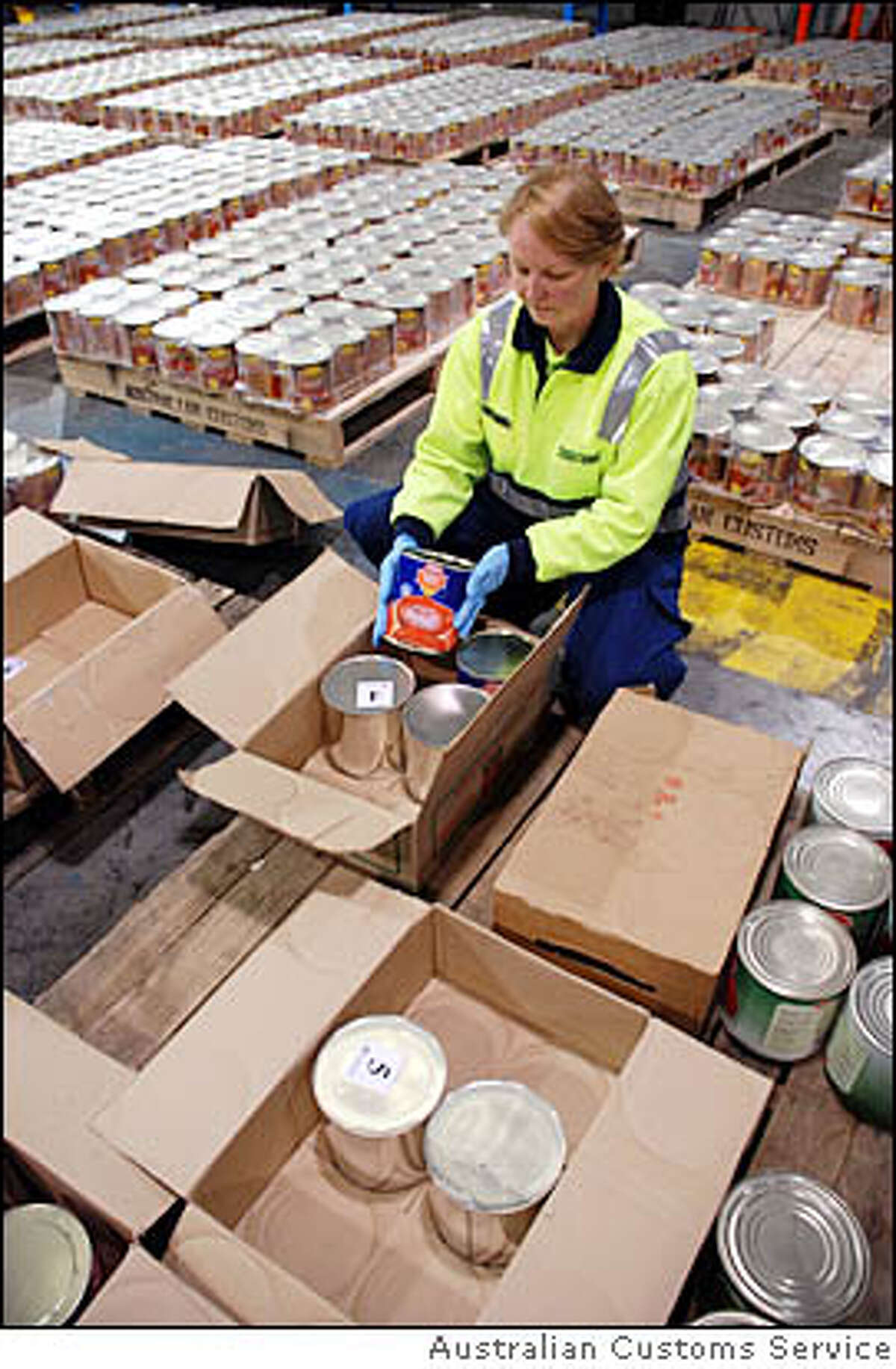 Canned tomatoes In this photo supplied by the Australian Customs Service, an unidentified customs agent unpacks tins disguised as canned tomato holding thousands of ecstasy tablets at a warehouse in Melbourne, Australia, Friday, Aug. 8, 2008. Australian Federal Police said Friday they have busted an international drug ring and seized nearly 5 tons of ecstasy in what they have called