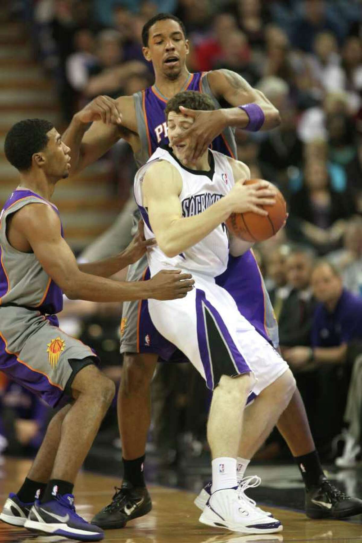 Sacramento Kings guard Jimmer Fredette, center, is double-teamed by Phoenix Suns Ronnie Price, left, and Channing Frye during the third quarter of an NBA basketball game in Sacramento, Calif., Saturday, Feb. 11, 2012. The Suns won 98-84.