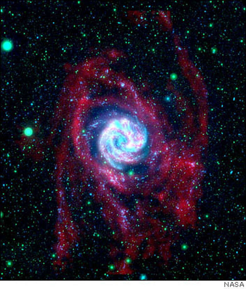 The Southern Pinwheel galaxy is shown in this composite image from NASA's Galaxy Evolution Explorer and the National Science Foundation's Very Large Array in New Mexico.The Galaxy Evolution Explorer observations, shown here in blue and green, highlight the galaxy's farthest-flung clusters of young stars up to 140,000 light-years from its center. The Very Large Array observations show the radio emission in red, highlighting gaseous hydrogen atoms, or raw ingredients for stars, which make up the lengthy, extended arms.